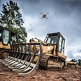 Microdrones md4-3000 mdLiDAR3000 performing a Laser scan of a construction site, flying over a bulldozer