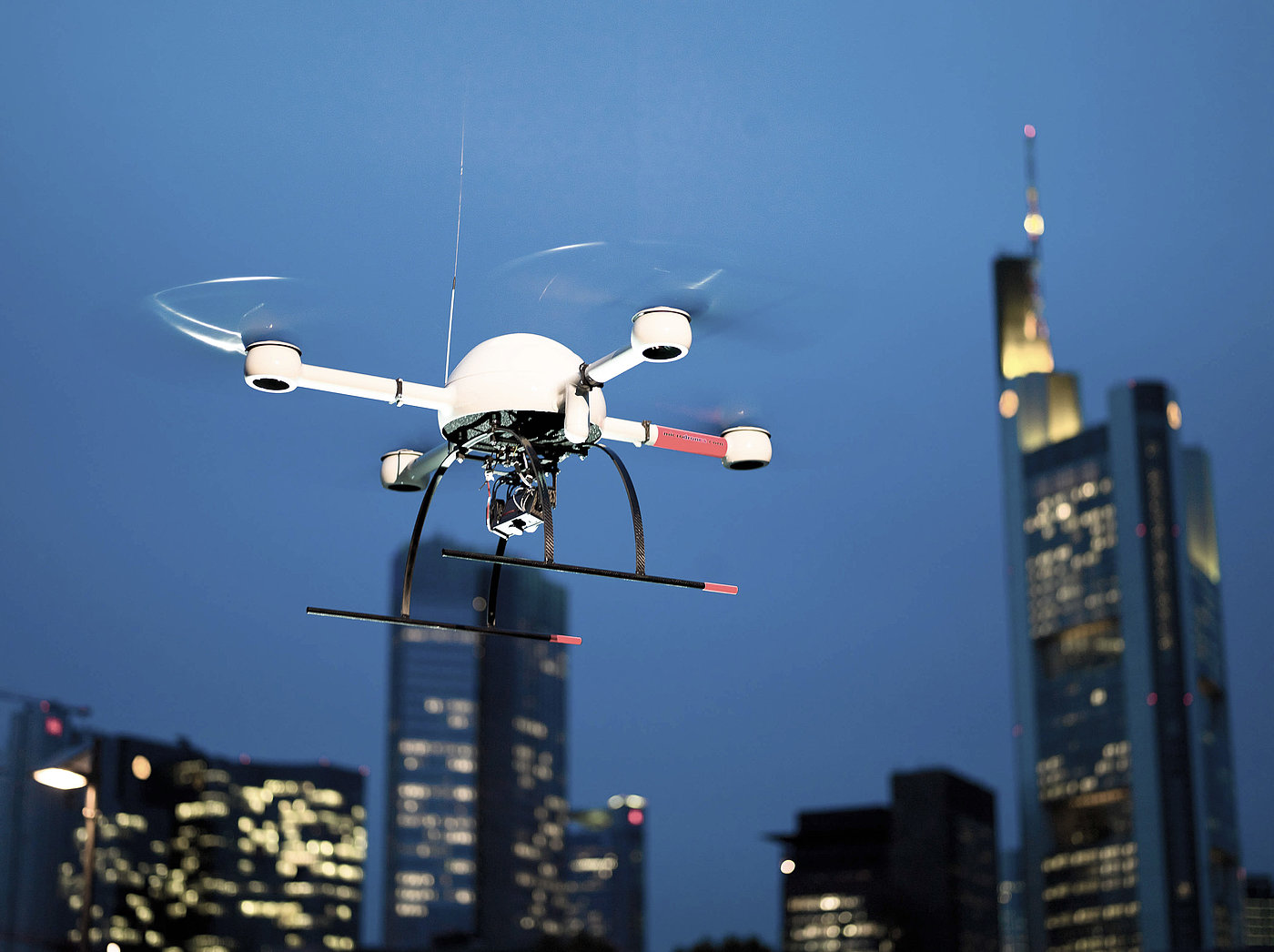 Microdrones md4-1000 during a surveillance flight, seen against the night skyline of Frankfurt, Germany