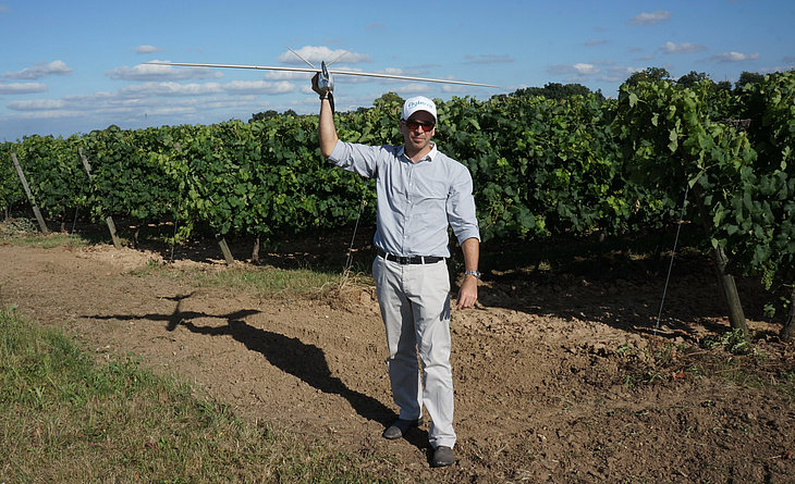 Vivien Heriard-Dubreuil, Microdrones president, holding a model aircraft ready to inspect a vineyard.